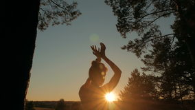 Woman practicing yoga in forest at sunset