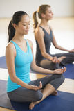 Woman Practicing Yoga With Friend At Health Club Royalty Free Stock Images