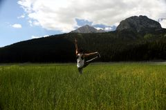 Woman practicing yoga in the grass. The picture was taken in the grass on Black Lake in Zabljak municipium. The model was certificated Yoga instructor Milica Royalty Free Stock Images