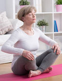 Woman practicing yoga at home. Mature stressed woman practicing yoga at home Stock Images