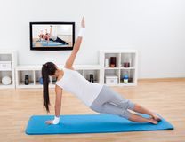 Woman practicing yoga at home Stock Images