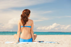 Woman practicing yoga lotus pose on the beach Royalty Free Stock Photo