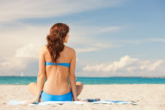 Woman practicing yoga lotus pose on the beach Stock Images