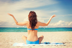 Woman practicing yoga lotus pose on the beach Stock Photography
