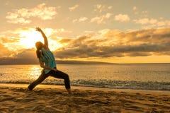 Yoga on a Maui Beach at Sunset. A woman practicing yoga on a Maui beach at sunset Royalty Free Stock Image