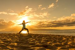 Practicing Yoga on a Maui Beach at Sunset. A woman practicing yoga on a Maui beach at sunset Royalty Free Stock Photos