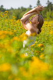 Woman practicing yoga in meadow of yellow flowers Stock Photos
