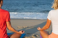 Woman practicing yoga and meditating on the beach. Close-up female hand in mudra and lotus position stock image