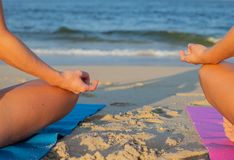 Woman practicing yoga and meditating on the beach. Close-up female hand in mudra and lotus position stock photography