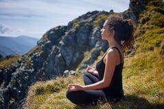 Woman practicing yoga on mountain Royalty Free Stock Photos