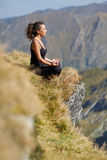 Woman practicing yoga on mountain Royalty Free Stock Photography