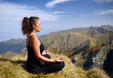 Woman practicing yoga on mountain Royalty Free Stock Photos