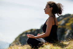 Woman practicing yoga on mountain Royalty Free Stock Image