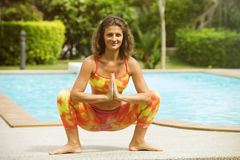 Woman is practicing yoga near the pool Stock Photography