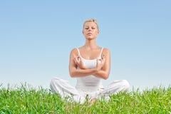 Woman practicing yoga outdoors Stock Photos