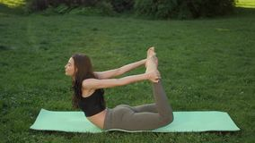 Woman practicing yoga outdoors in park stock video footage