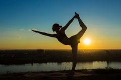 Woman practicing yoga in the park at sunset - lord of the dance pose. Silhouette of sporty woman practicing yoga in the park at sunset - lord of the dance pose Stock Image