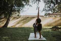 Woman practicing yoga in the park royalty free stock images
