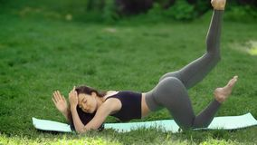 Woman practicing yoga outdoors in park. Woman practicing yoga performing yoga-asanas with closed eyes. Young attractive slim girl in bodysuit relaxing and doing stock video