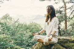 Woman practicing yoga in pose of lotus in forest. Stylish beautiful young woman practicing yoga in pose of lotus on cliff in summer forest outdoor stock photography