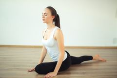 Woman practicing yoga pose at yoga healthy sport gym stock photography