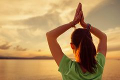 Woman practicing yoga with praying gesture in front of sea. Unrecognizable young woman practicing yoga with praying gesture in front of sea at sunset outdoor stock photography