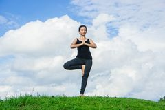 Woman practicing yoga relax in nature and blue sky background Royalty Free Stock Photo