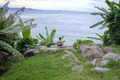 Woman practicing yoga on a rock in front of the beach stock image