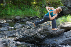 Woman practicing yoga on rocks beside stream Royalty Free Stock Photo