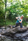 Woman practicing yoga on rocks beside stream Royalty Free Stock Image
