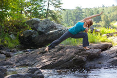 Woman practicing yoga on rocks beside stream Stock Images