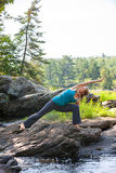 Woman practicing yoga on rocks beside stream Stock Photo