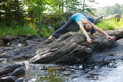 Woman practicing yoga on rocks beside stream Stock Photography
