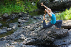 Woman practicing yoga on rocks beside stream Stock Photos