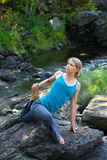 Woman practicing yoga on rocks beside stream Royalty Free Stock Photos