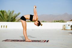 Woman practicing yoga on the roof with palm trees royalty free stock photos