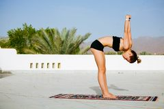 Woman practicing yoga on the roof with palm trees royalty free stock photography