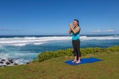 Woman Practicing Yoga on the Scenic Maui Coast. A woman practicing yoga along the scenic coast of Maui Hawaii Royalty Free Stock Photo