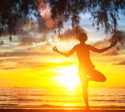 Woman practicing yoga by the sea beach at sunset. Royalty Free Stock Photos