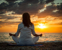 Woman Practicing Yoga by the Sea at Sunset Royalty Free Stock Image