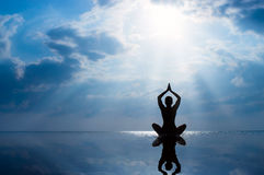 Woman practicing yoga, silhouette on the beach at sunset Royalty Free Stock Image
