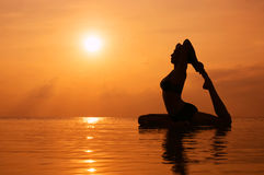 Woman practicing yoga, silhouette on the beach at sunset Royalty Free Stock Photography