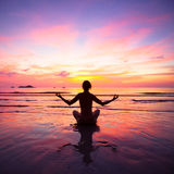 A woman practicing yoga sitting on the beach Stock Images