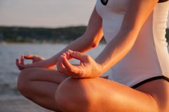 Woman is practicing yoga sitting in Lotus pose at sunrise. Silhouette of woman meditating on the beach. Woman is meditating on the calm beach at sunset. Woman is royalty free stock photography