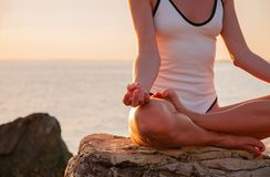 Woman is practicing yoga sitting in Lotus pose at sunrise. Silhouette of woman meditating at sunset on the beach. Woman is meditating on the calm beach at sunset royalty free stock photo