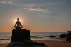 Woman is practicing yoga sitting on stone in Lotus pose at sunset. Silhouette of woman meditating on the beach. Woman is meditating on the calm beach at sunset stock images