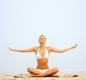 Woman practicing yoga by stretching Royalty Free Stock Photography