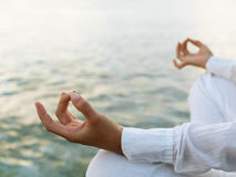 Woman practicing yoga at sunrise. Near the ocean Royalty Free Stock Image