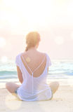 Woman practicing yoga at sunrise beach. Young caucasian woman practicing yoga at sunrise beach Stock Photography