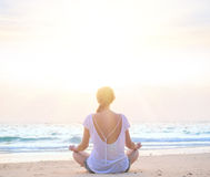 Woman practicing yoga at sunrise beach. Young caucasian woman practicing yoga at sunrise beach Royalty Free Stock Photography